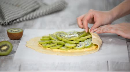 tartlet : Female hands making galette with fresh kiwi.
