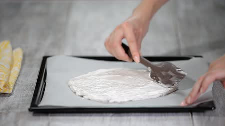 geçiştirmek : Female hand spreads the batter on a baking sheet.