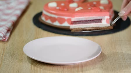 eper : Piece of red berry mousse cake on a plate. Beautiful decorated Heart-shape Mousse cake, on Valentines Day.
