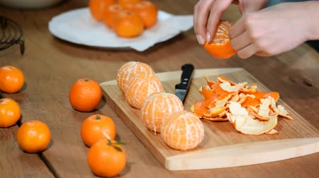 refresco : Woman hand peeling ripe sweet tangerine, close up.