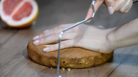konfekció : Female pastry chef is slicing a cake on table.