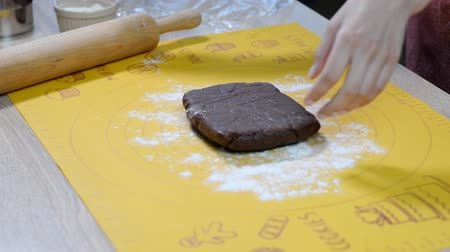 tekercselt : The confectioner rolls out the chocolate dough with a rolling pin.