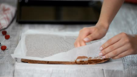 cacao : Female hands peeling the parchment paper from the bottom of the sponge cake.