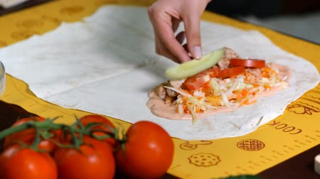 соленья : Making a shawarma or doner kebab with chicken meat and vegetables, wrapping in flat bread. Preparation of lavash to shawarma.