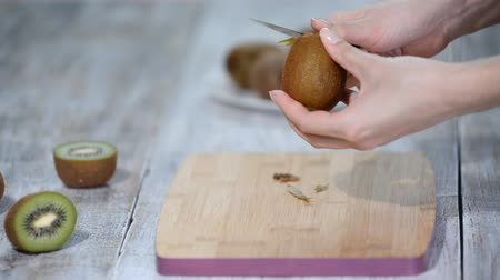 кухонная посуда : A woman cleans the kiwi peel with a knife on a wooden background.