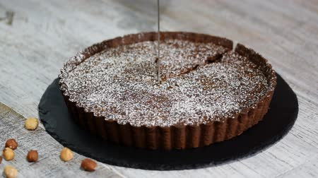 calorias : Cutting homemade dark chocolate tart on rustic background.