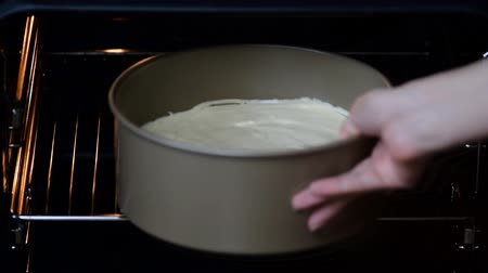 чизкейк : The woman puts the cake in the oven. Womans hands in kitchen gloves put tray with uncooked cake into electrical oven.
