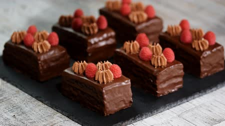 jegesedés : Female hands decorating chocolate cakes with fresh raspberry.
