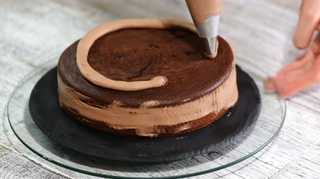 çırpılmış : Close-up: biscuit cream in the form of a spiral on the cake. Chocolate sponge cake with cream. Preparation of cake in a candy store. The food for the holiday. Stok Video