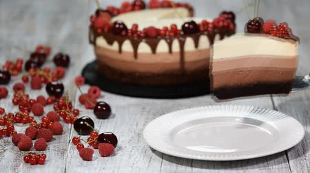 souffle : Piece of delicious three chocolate mousse cake decorated with fresh berry. Stock Footage