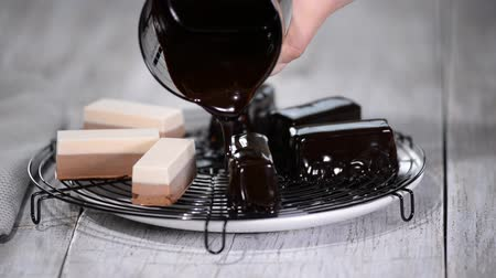 avantajado : Pour the chocolate mirror glaze on a delicious mousse dessert. Liquid tasty sweet dessert cooking. Stock Footage
