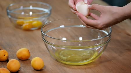 хрупкий : Woman hands breaking an egg to separate egg white and yolks Стоковые видеозаписи