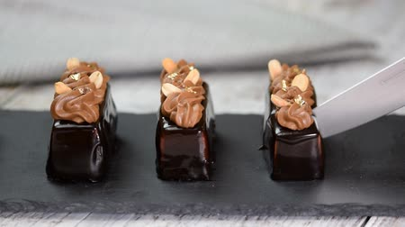 envidraçado : Mini mousse pastry dessert covered with chocolate glaze and peanuts. Modern european cake. French cuisine.