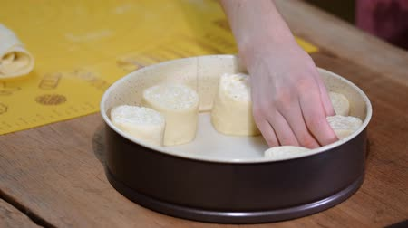 cheese making : Female baker is putting buns to baking sheet, close up.