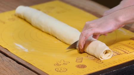 pergament : Woman cutting dough for cinnamon rolls on table, closeup Stock mozgókép
