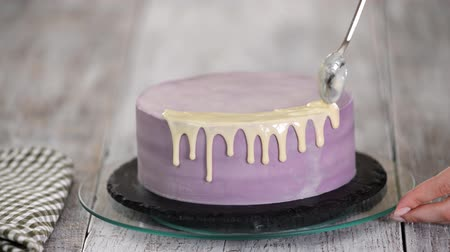 fondant : Close-up of preparing a cake in the kitchen, pouring white chocolate glaze on the cake.