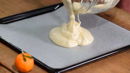 pergament : Pouring cake batter onto baking sheet.
