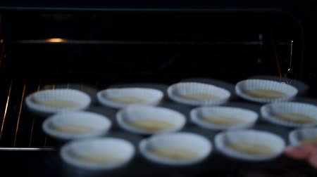 hard boiled : Woman putting muffin tin with batter into oven