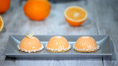 застекленный : Decorate with white chocolate modern orange mousse cakes with mirror glaze.