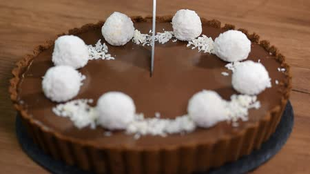 arduvaz : Cutting a piece of chocolate coconut tart.