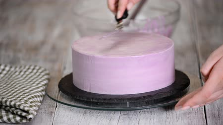 amoras : The process of decorating a cake with purple cream cover. Confectioner equates biscuit cream using pastry spatula. Stock Footage