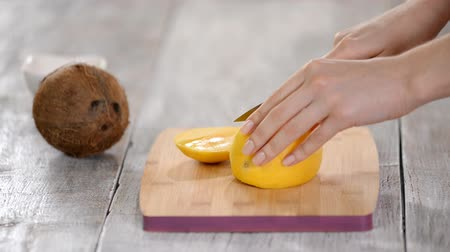 manga : Female Chefs hands cutting mango on wooden cutting board. Stock Footage