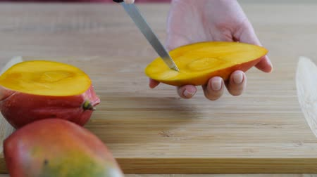 pansuman : Female Chefs hands slice mango on wooden cutting board.