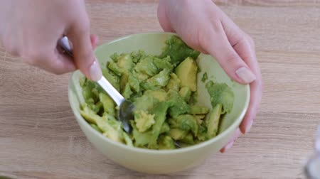 mashing : Close-up Of Woman Hands Mashing Avocado With Fork In Bowl.