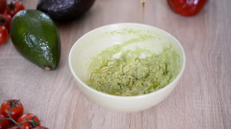 habanero : The cook pours olive oil into a bowl of guacamole. Healthy food concept. Stock Footage