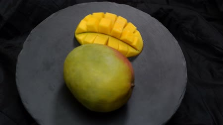 jus d orange : Organische tropische vruchten, close-up dia's mango's op zwarte plaat. Stockvideo