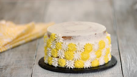 buttercream : Chef or baker decorating cake with whipped cream.