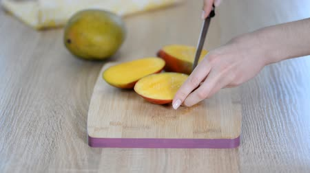 кухонная посуда : Closeup of woman cutting mango