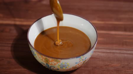 caramelo : Bowl of melted caramel sauce on wooden table