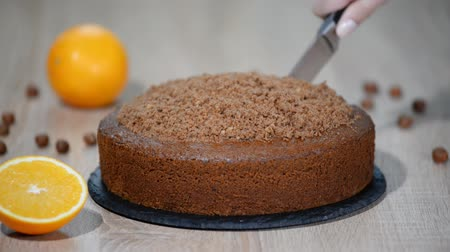 испечь : A woman is cutting a chocolate cake