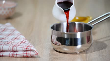 megőriz : Woman pouring cherry juice in a saucepan. Stock mozgókép