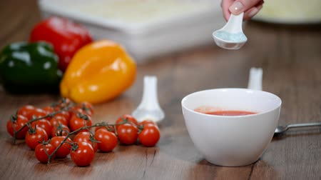 chilli sauce : Woman in kitchen making a tomato sauce. Add spices to tomato puree