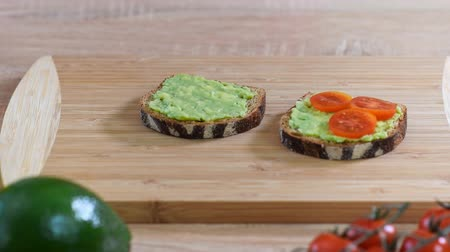 manteiga : Top view of making avocado toast with tomatoes on a wood cutting board Vídeos