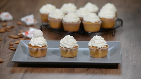 konfekció : Freshly baked vanilla cupcake with coconut frosting. Decorating cupcakes with coconut truffles
