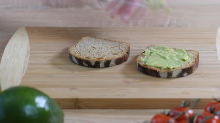 quebra : Making avocado toast. Woman spread avocado on toasted sandwich bread. Top view
