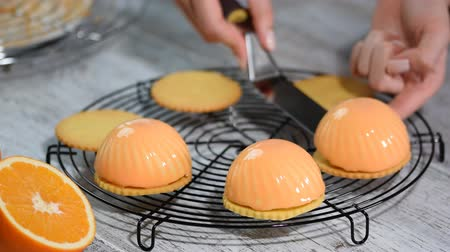 konfekció : French pastry with mirror glaze. French mousse cake with shiny glaze on a wooden table. Modern european cake pastry.
