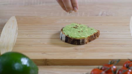 len : Toast with avocado, sesame and flax seeds on rustic wooden background. Healthy breakfast.