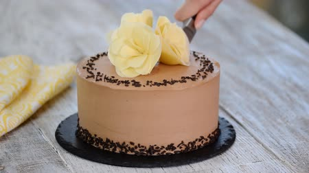 fondán : Cutting of chocolate cake on plate. Chocolate cake decorated white chocolate flowers. Dostupné videozáznamy