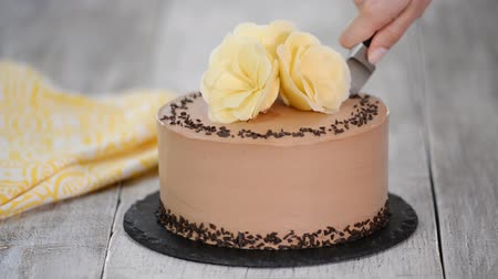 geçiştirmek : Cutting of chocolate cake on plate. Chocolate cake decorated white chocolate flowers. Stok Video