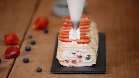 şekerleme : Woman piping cream over meringue roulade. Process of making meringue roll Stok Video