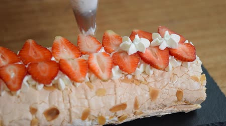 pavlova : Woman piping cream over meringue roulade. Process of making meringue roll. Stock Footage