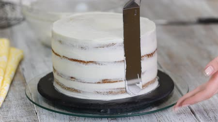 konfekció : Confectioner makes a cake with white cream at kitchen