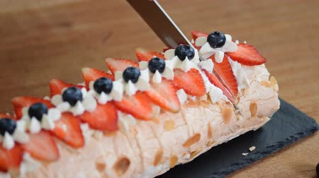 pavlova : Close up, young girl is cutting meringue roulade with berries and mascarpone.