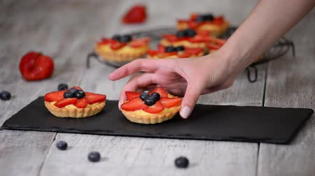 blueberry cheesecake : Summer berry tartlets with cream and fresh berries. Healthy summer pastry dessert for party. Stock Footage