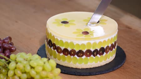 açoitado : Cutting with a knife mousse cake with grapes. Round mousse cake decorated with grapes.