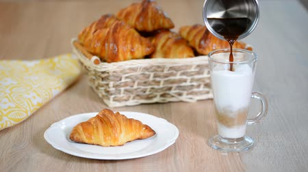 mouth watering : Women poured espresso in a milk cup to make a latte next to butter croissant.